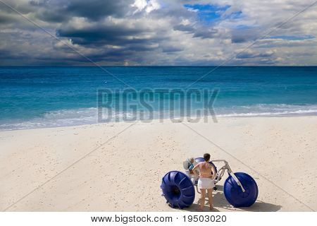 Woman and child on an empty beach with a tricycle peddle boat.