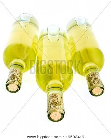 Three bottles of white wine isolated on white.