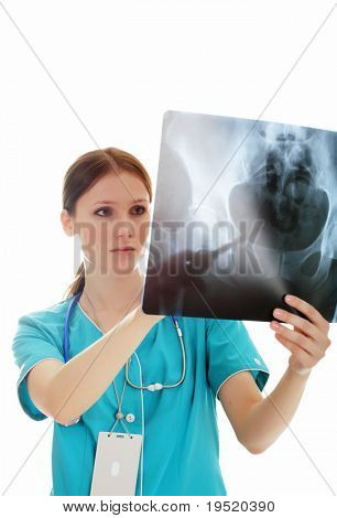 Portrait of thoughtful female doctor in the green uniform looking at the x-ray image.