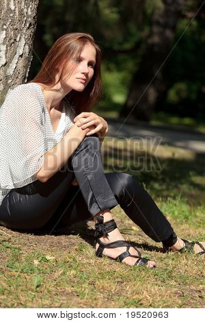 pretty woman under big tree in sunny day