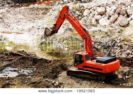 Excavator standing in sandpit with risen bucket