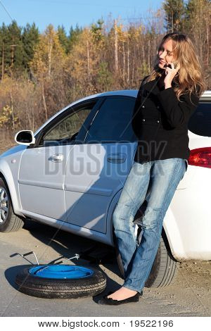 Young woman standing by her damaged car and calling for help