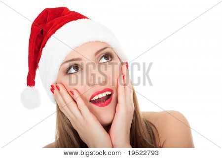 Surprised beautiful young woman wearing santa hat. Isolated over a white background.