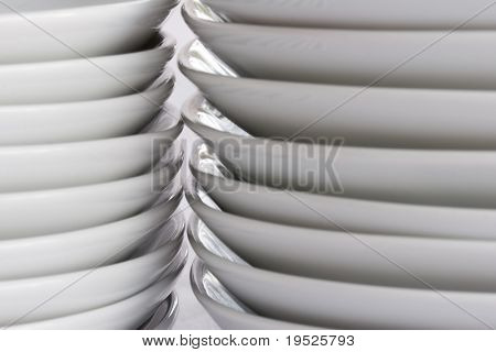 stacks of white plates up close