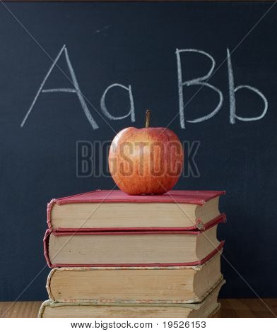 apple, textbooks, and ABCs on a blackboard