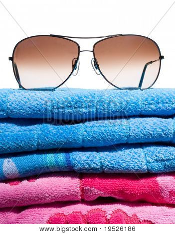 aviator sunglasses on a stack of beach towels - isolated on white