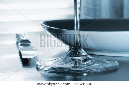 dinner setting - close-up of knife, glass, plate - toned