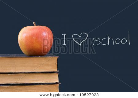 I 'heart' school written on chalkboard with apple, books