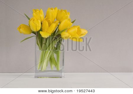 bouquet of yellow tulips in vase on table - grey background