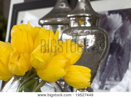 yellow tulips in vase with home decor accessories & artwork in background - tablescape