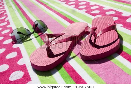 pink flip flops and aviator sunglasses on pink and green towel