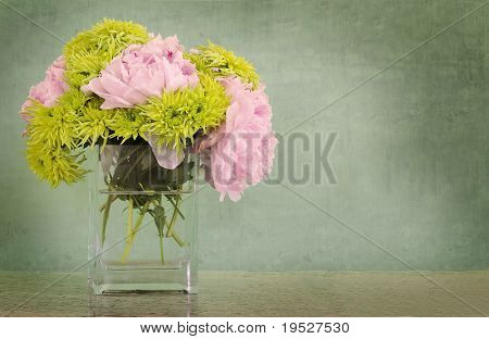 pink peonies and chartreuse chrysanthemums in vase on countertop