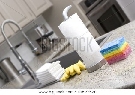 sponges, paper towels, gloves, cloths in modern kitchen for housework - narrow depth of field
