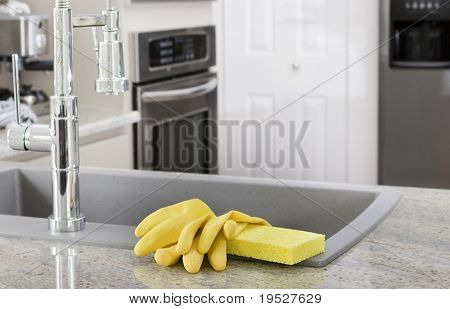 yellow gloves and sponge on sink in modern kitchen - housekeeping