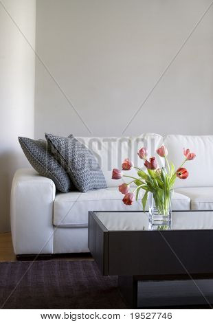 vase of red tulips in modern white living room - home decor