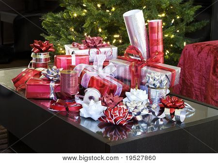 red and white christmas presents with bows on coffee table by tree