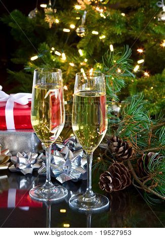 two glasses of champagne on green christmas background and gifts