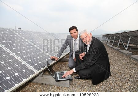 Businessmen checking solar panels running