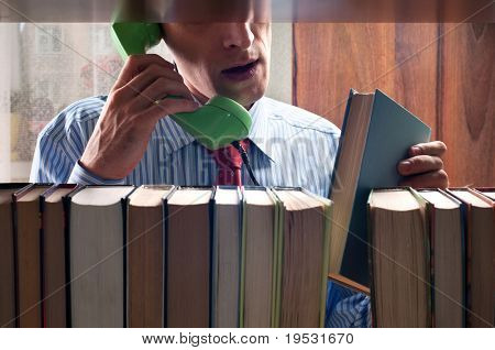 men talking by phone and a book next to the bookshelf
