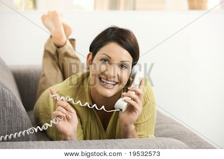 Happy woman chatting on phone, lying on sofa, smiling.?