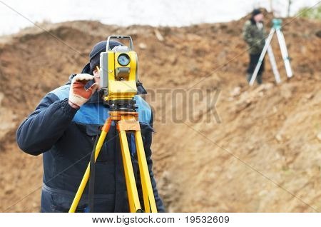 Surveyor worker make data collection with total station theodolite at construction site