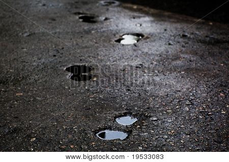 Abstract trace of shoes on asphalt background just after the rain.  Lights are reflected in a puddle and the wet surface. Focus on first plan.