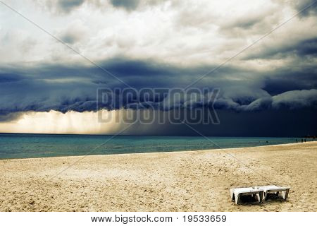 Stormy weather with rain on the beach with two chairs. Before a powerful storm.
