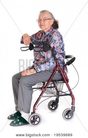 Serious senior citizen woman in combination walker/wheelchair, isolated on a white background.