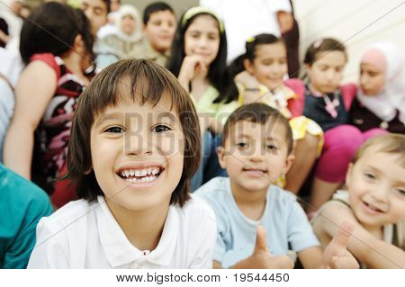 Large group, crowd, lot of happy children of different ages, summer outdoor sitting