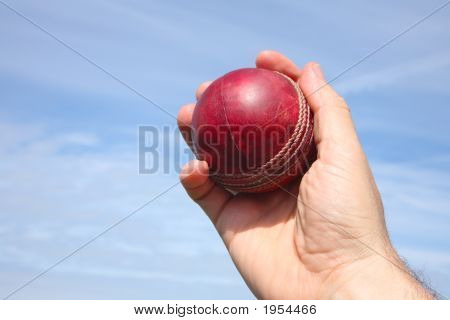 Close Up Of A Cricket Ball Being Caught Against A Blue Sky.