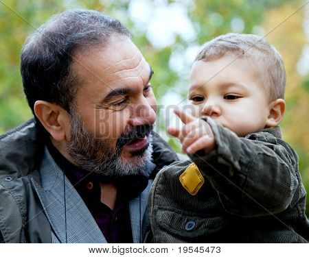 Close-up child being held by grandfather pointing forward