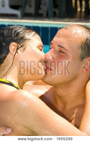 An Attractive Couple Kissing By The Pool
