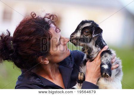 Jovem mulher com bebê cabra ao ar livre