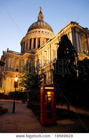 Red London Telephone box in front of St. Paul's cathedral in the evening
