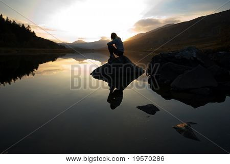 Beautiful girl on mountain lake at sunset