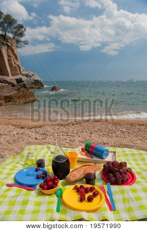 tasty food on colorful plastic crockery at the beach