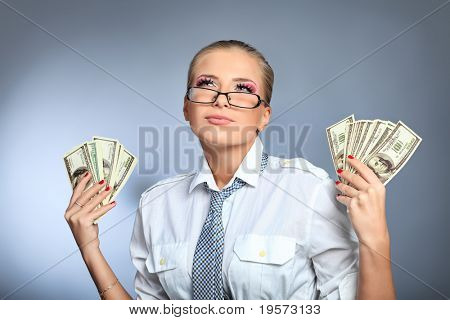 Beautiful businesswoman holding money. Studio shot over grey background.