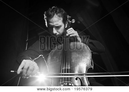 Dramatic portrait of cellist playing classical music on cello on black background. Copyspace.