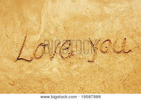 love you handwritten in sand on a beach