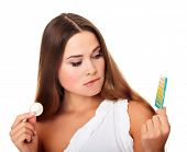 stock photo of contraception  - Confused pretty caucasian girl looking at condom and contraceptive pills - JPG