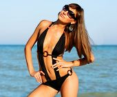 Beautiful Long Hair Young Woman In Black Swimwear And Sunglasses On The Sea Coast Beach, Close Up Ou poster