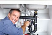 image of plumber  - Young plumber fixing a sink at kitchen - JPG