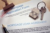 Mortgage loan agreement application with  key on house shaped keyring poster