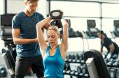 Trainer helping athletic woman at gym. Personal trainer giving weightlifting training to girl in gym poster