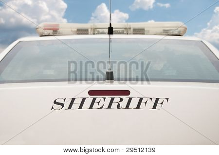 Rear end of a sheriff's patrol car with cloudy sky background
