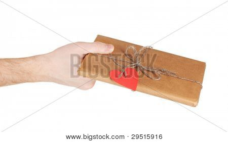 Parcel with blank heart-shaped label in man's hand isolated on white