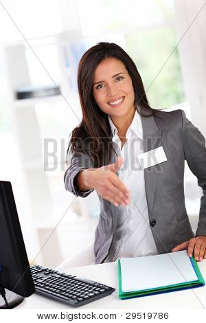 Portrait of beautiful smiling hostess giving handshake