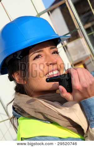 Site manager using walkie-talkie on building site