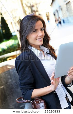 Young woman connected on internet in town