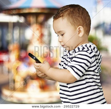 portrait of a funny kid touching a mobile against a carousel background